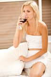Woman having wine in bed Stock Photos