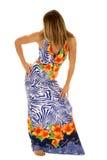 Woman in hawaiin dress head turned. A woman in her hawaiin dress with her hand on her hip Stock Image