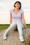 Woman on hay bale Stock Image