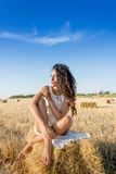 Woman on hay bale in field Stock Image
