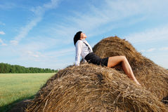 Woman on hay bale in summer field.  Royalty Free Stock Photos