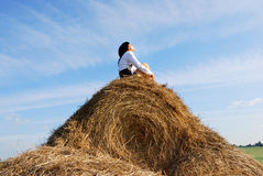 Woman on hay bale in summer field Stock Images