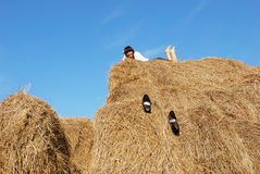 Woman on hay bale in summer field Stock Photo