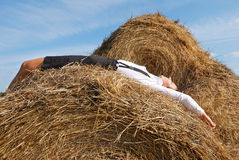 Woman on hay bale in summer field Royalty Free Stock Photo