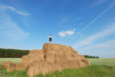 Woman on hay bale in summer field. Enjoying a warm windy day Royalty Free Stock Images