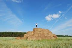Woman on hay bale in summer field. Enjoying a warm windy day Stock Image