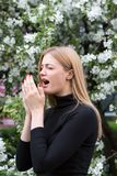 Woman reacts with asthma on hay fever while being in park Royalty Free Stock Photography