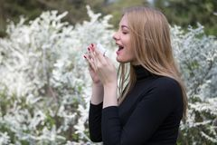 Woman with hay fever in front of white flowers Royalty Free Stock Photo