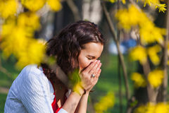 Woman with hay fever. Young woman sneezing when standing close to flowers in the spring Royalty Free Stock Photo