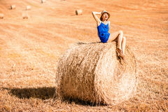 Woman on the hayfield. Young woman in blue dress enjoying nature on the hayfield in Tuscany in Italy Royalty Free Stock Photography