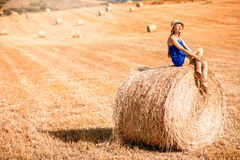 Woman on the hayfield. Young woman in blue dress enjoying nature on the hayfield in Tuscany in Italy Stock Images