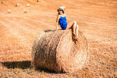 Woman on the hayfield. Young woman in blue dress enjoying nature on the hayfield in Tuscany in Italy Royalty Free Stock Images