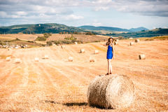 Woman on the hayfield. Young woman in blue dress enjoying nature on the hayfield in Tuscany in Italy Stock Image