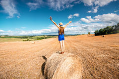 Woman on the hayfield. Young woman in blue dress enjoying nature on the hayfield in Tuscany in Italy Stock Photography