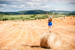 Woman on the hayfield. Young woman in blue dress enjoying nature on the hayfield in Tuscany in Italy Royalty Free Stock Image