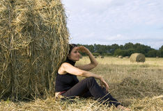 Woman about a haystack Stock Photography