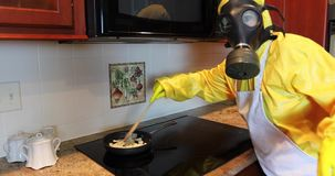 Woman in Haz Mat cooking onions stock video footage
