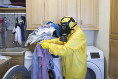 Woman in Haz Mat suit sorting laundry Stock Images