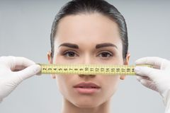 Woman head being measured by beautician hands Stock Photo