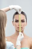Woman head being measured by beautician hands Royalty Free Stock Image
