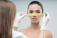 Woman head being measured by beautician hands Stock Images