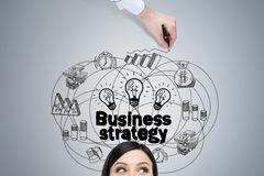 Woman head and business strategy. Close up of a head of a woman with black hair standing near a gray wall with a and business strategy sketch drawn by a hand of Stock Images