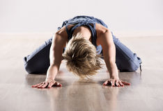 Woman with head down while stretching hip muscles Royalty Free Stock Image