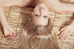 Woman head and hands on bamboo mat Royalty Free Stock Images