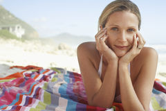 Woman With Head In Hands Lying On Blanket At Beach Stock Images