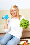 Woman with a head of lettuce and dumb-bell Stock Images