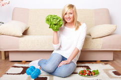 Woman with a head of lettuce and dumb-bell Royalty Free Stock Image