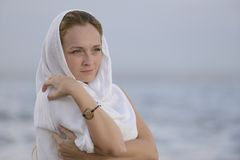 Woman with head scarf on the beach. Pensive woman with head scarf on the beach Stock Images