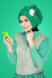 Woman with head scarf holding mobile phone Stock Photography