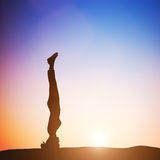 Woman in head stand yoga pose meditating at sunset. Zen Stock Photography