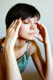 Woman with Headache. Young woman with closed eyes massaging her head Stock Images