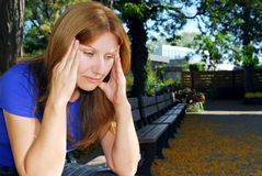 Woman with headache. Mature woman with a headache sitting on the park bench Stock Photo