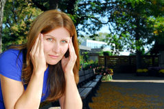 Woman with headache. Mature woman with a headache sitting on the park bench Royalty Free Stock Photo