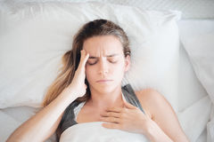Woman with headache in bed Stock Photos