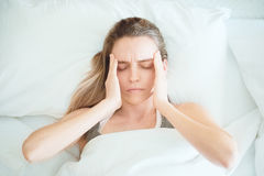 Woman with headache in bed, stress Royalty Free Stock Photography