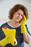 Woman with a headache after cleaning the house Royalty Free Stock Image