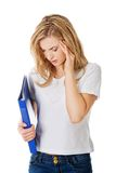 Woman with headache holding a binder.  Stock Photography