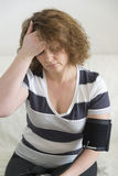 Woman with headache measures a  blood pressure Stock Photos