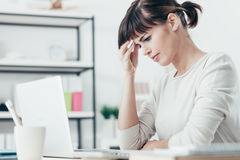 Woman with headache in the office Stock Photography