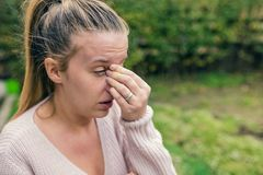 Woman with headache. Seasonal allergies and health problems. Sin. Us ache causing very paintful headache. Unhealthy woman in pain. Sharp strong sore. Flu cold or Royalty Free Stock Image
