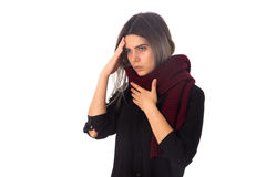 Woman with headache and sore throat. Young woman in black shirt with long scarf having a headache and sore throat on white background in studio Stock Photos