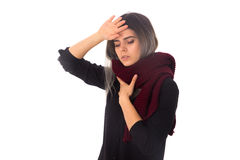 Woman with headache and sore throat. Young woman in black shirt with long vinous scarf having a headache and sore throat on white background in studio Royalty Free Stock Photography