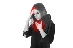 Woman with headache and sore throat. Young woman in black shirt with scarf having a headache and sore throat on white background in studio Royalty Free Stock Photography