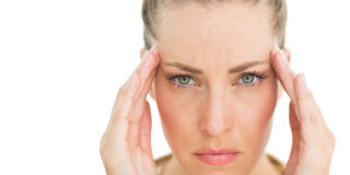 Woman with headache touching her temples frowning at camera Royalty Free Stock Photography