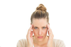 Woman with headache touching her temples looking at camera Stock Image