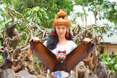Woman in headdress holding a flying fox